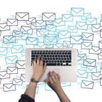 Kleine blaue und schwarze Briefumschläge, die nebeneinander und teilweise aufeinander skizziert sind. Darüber das Unterteil eines Laptops mit Tastatur und Mousepad. Zwei Hände ragen vom unteren Bildrand in die Mitte und nutzen das Bedienfeld