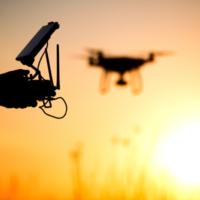 Im Hintergrund fliegt eine Drohne vor dem Sonnenuntergang. Vorne sind die Konturen eines Menschen mit der Fernsteuerung in den Händen zu sehen.