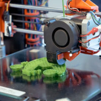 Zu sehen ist ein 3D-Drucker bei der Arbeit. Unter dem Druckkopf liegt ein grünes Gebilde auf dem Tisch