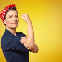 Vor gelbem Hintergrund ist eine brünette Frau abgebildet. Auf dem Kopf trägt sie ein zusammengeschnürtes rotes Tuch mit weißen Punkten. Die Ärmel ihres blauen Pullovers sind hochgekrempelt. Den rechten Arm angewinkelt streckt sie ihre Faust in die Höhe. Die linke Hand liegt dabei auf dem rechten Bizeps.