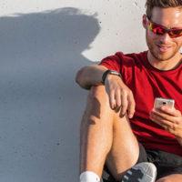 Ein Mann in Fitness-Kleidung sitzt mit einem Smartphone in der Hand vor einer Mauer. Auf die Mauer fällt sein Schatten.