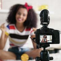 Ein junge Frau mit südländischem Aussehen sitzt lächelnd vor einer Videokamera im Vordergrund. Sie nimmt ein Video-Tutorial für ihren Online-Blog auf.