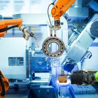 Roboterarme in Orange, Blau und Grün arbeiten gemeinsam an einer runden Scheibe aus Metall