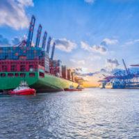 Ein Bild des Hamburger Hafens. Vorne ein Containerschiff, rechts im Hintergrund die Krananlagen