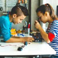 Ein Junge und ein Mädchen sitzen an einem Tisch und basteln an einem elektronischen Gerät herum, das man nicht genau erkennen kann.