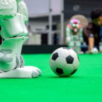 Im Vordergrund ist ein grüner Kunstrasen zu sehen. Außerdem ein Fußball und die Beine eines Roboters. Im Hintergrund kniet eni junger Mann, unscharf fotografiert, der die Szene zu beobachten scheint.