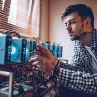 Auf dem Foto sitzt ein Mann zwischen 20 und 30 Jahren mit einem blaukarierten Hemd vor mehreren Festplatten oder Platinen, die in Reihe hintereinander geschaltet sind.
