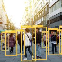 """Blick in eine Fußgängerzone, Innenstadt irgendwo auf der Welt. Die Menschen, die sich dort bewegen, sind von gelben großen Quadraten eingerahmt. Diese stehen als Symbol für Kameras im öffentlichen Raum, die alle Bewegungen von Menschen """"beobachten"""""""