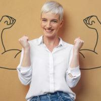 Auf dem Foto ist eine Frau zu sehen, weiße Bluse, kurze helle Haare. Sie hat die Arme angewinkelt, als ob sie die Muskeln kräftig anspannen will. Sie steht vor einer braunen Wand, auf der zwei Arme mit muskulösen Bizeps zu sehen sind