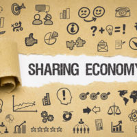 """Ein hellbraunes Packpapier wurde aufgekratzt und ein Stück aufgerollt: Darunter kommt der Schriftzug """"Sharing Economy"""" zum Vorschein. Auf dem braunen Papier befinden sich viele hingekritzelte Symbole"""