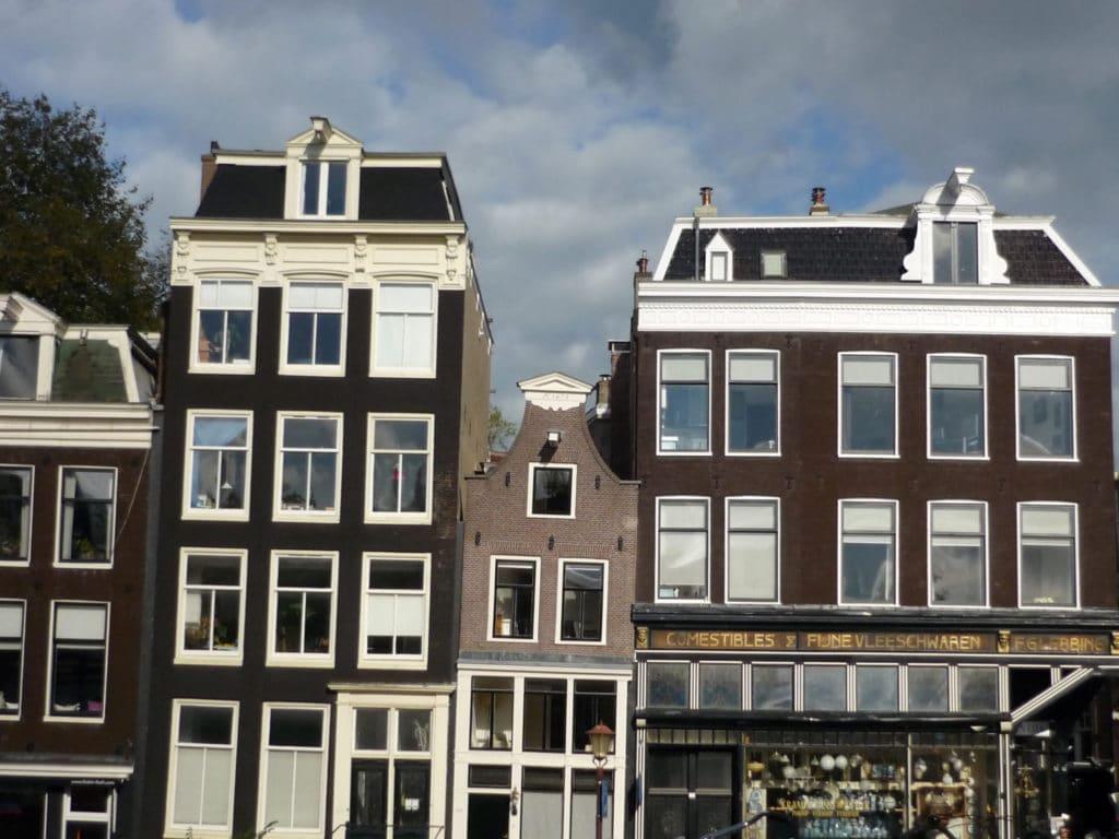 Das Bild zeigt eine typische Häuserfront in Amsterdam: drei schmale braune, etwas schiefe Häuser, Giebel. Ein Haus ist sehr schmal, das andere etwas breiter. Vorne rechts ist ein Laden zu sehen. Der Himmel ist etwas bewölkt, graue Wolken vor blauem Hintergrund.