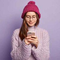 Vor einem fliederfarbenen Hintergrund steht eine junge Frau. Sie hat eine Wollmütze auf ihrem langen Haar, das über ihre rechte Schulter fällt. In den Händen hält sie vor ihrer Brust ein Smartphone. Sie lächelt und scheint Spaß zu haben.