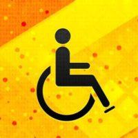 Vor einem gelb-orangenen Hintergrund befindet sich ein schwarzes Icon: Ein Strichmännchen sitzt in einem Rollstuhl. Dies ist ein Symbolbild