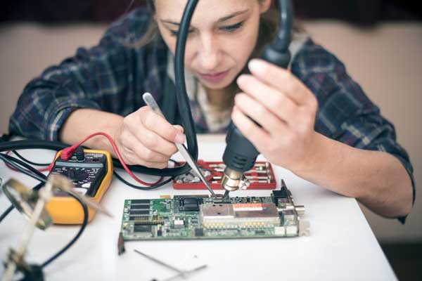Eine junge Frau in einem karierten Hemd sitzt vor einer Computerplatine. Sie hat ein Lötgerät in den Händen und scheint etwas zu reparieren