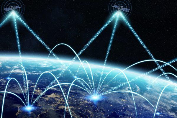 Das Foto zeigt den Blick auf Satelliten, die über der Erde im Weltall schweben. Helle Linien verbinden die Satelliten mit verschiedenen Punkten auf der Erde, so dass man deutlich ein weltumspannendes Netzwerk erkennt