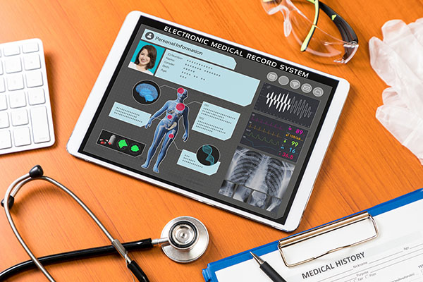 Auf einem Holztisch liegt ein Tablet mit einer geöffneten medizinischen App. Daneben befinden sich ein Stetoskop, eine Laborbrille, Gummihandschuhe und ein Klemmbrett