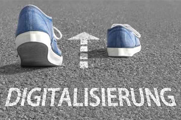 """Zu sehen ist ein Straßenpflaster. Darauf sind zwei Schuhe so drapiert, dass es aussieht, als ob sie von alleine gehen. In der Mitte befindet sich ein weißer Pfeil, der wie eine Straßenmarkierung aussieht. Davor steht das Wort """"Digitalisierung"""""""
