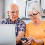 Ein Senior und eine Seniorin sitzen mit einem Smartphone vor einem Computer.