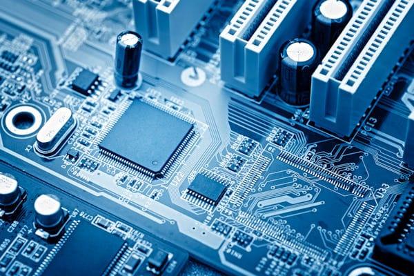 Zu sehen ist ein Mikrochip. Auf eine Platine sind runde und eckige Objekte aufgesetzt. Diese sind mit vielen kleinen Drähten miteinander verbunden.