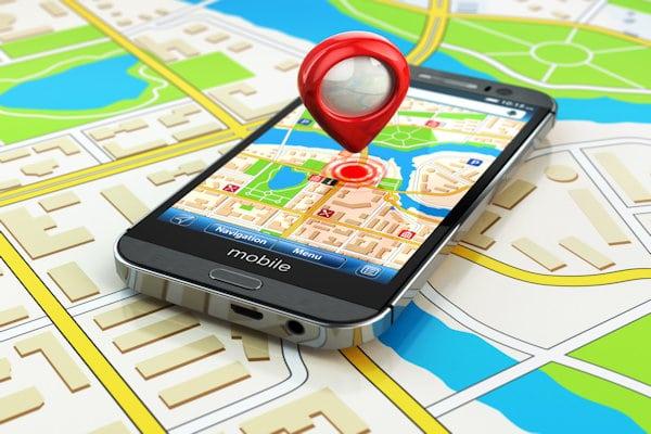 Ein Smartphone liegt auf einer Landkarte. Eine solche ist auch auf dem Display zu sehen. Darüber schwebt ein Pin, der einen Punkt markiert. Dieser ist mit einem roten Kreis und mehreren Ringen dargestellt.