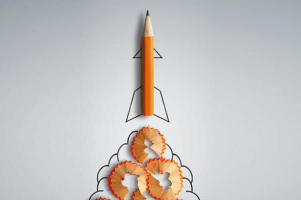 Vor grauem Hintergrund ist ein orangener Bleistift zu sehen. Die Mine ist nach oben gerichtet, unter dem Bleistifte liegen runde Anspitzreste. Schwarze Konturen vervollständigen das Ganze zu einer Abgaswolke. Der Bleistift soll wie eine Rakete abheben.
