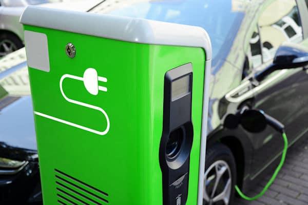 Auf dem Foto ist eine grüne Ladesäule für E-Autos zu sehen. Im Hintergrund steht ein Auto, das geladen wird.