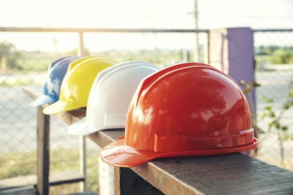 Eine Reihe von Bauhelmen in verschiedenen Farben liegen auf einer Holzplanke.