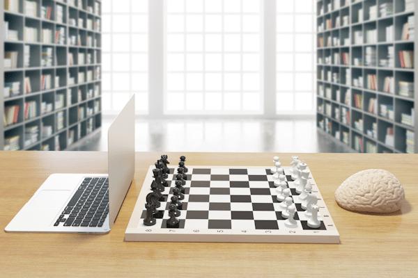 Ein Notebook und die Nachbildung eines Gehirns liegen auf einem Tisch. Dazwischen ein Schachbrett.