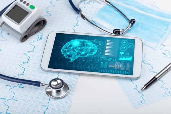 Kariertes Papier mit aufgezeichneten Herzfrequenzen, darauf ein Smartphone mit medizinischen Daten auf dem Display. Daneben liegen Stethoskop, Blutdruckmessgerät und Kugelschreiber.
