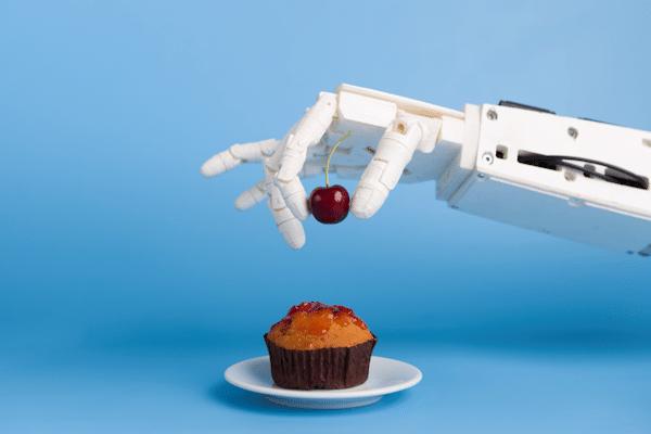 Illustration: Roboterhand legt Kirsche auf kleinen Kuchen